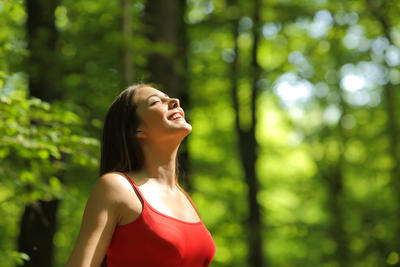 Woman breathing fresh air in a green forest in summer wearing a red shirt